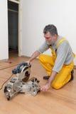 Laminate flooring of room, batten cuting. Worker cut wooden batten for laminate floor, floating wood tile royalty free stock image