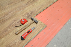 Laminate flooring of room. Flooring of room, laminate, foam and tools, hammer, meter, cutter stock photography
