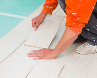 Laminate Flooring Technique. Handyman laying down laminate flooring boards while renovating a house Stock Image