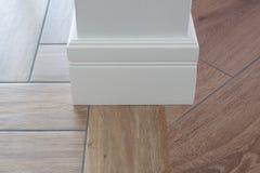 Tiles immitating hardwood flooring. Laminate parquete flooring, tiles immitating hardwood flooring. Cork compensator as an adapter. Light matte wall, white Stock Images