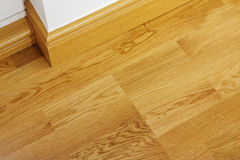 Laminate wooden flooring and skirting boards. Close up showing some laminate flooring and mdf imitation wood skirting boards in newly constructed house Royalty Free Stock Photos