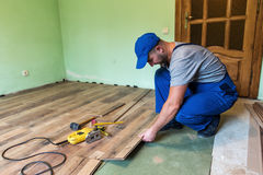 Laminate. Worker install the laminate floor stock image