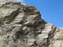 Laminated structure of mountain rock over blue sky Royalty Free Stock Photos