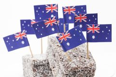 Lamingtons to Celebrate Australia Day. Close up of two lamingtons with a large number of Australian flags on top royalty free stock image