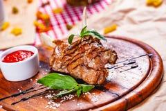 Lammkarree gebraten mit aromatischem Olivenöl, Kräutern und Gewürzen auf hölzernem Brett lizenzfreies stockfoto
