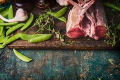 Lammkarree mit den grünen Erbsenhülsen, Vorbereitung auf rustikalen Hintergrund kochend, Draufsicht Stockfotografie