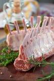 Lammkarree, rohes Fleisch mit dem Knochen auf rustikalem Küchentisch am hölzernen Hintergrund, Seitenansicht lizenzfreies stockfoto