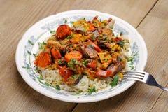 Lammragu med grönsaker och ris i den vita plattan Arkivbild