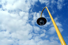 Lamp. Yellow rounded Lamp post against blue cloudy sky Stock Photo