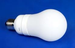 Lamp. Energy saving fluorescent lamp on blue background Stock Photo