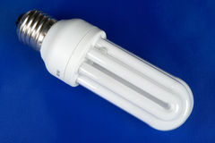 Lamp. Energy saving fluorescent lamp on blue background Royalty Free Stock Image