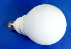 Lamp. Energy saving fluorescent lamp on blue background Royalty Free Stock Images