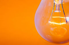 Lamp. Close up of light bulb against orange background - shallow depth of field Stock Photo