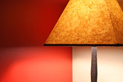 Lamp. A Lamp with an orange shade against a red and beige wall Royalty Free Stock Images