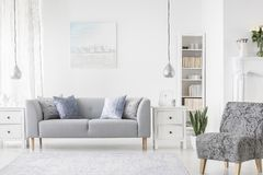 Lamp above white cabinet between plant and grey sofa in simple flat interior with armchair. Real photo royalty free stock image
