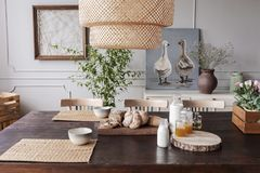 Lamp above wooden table with food and bowls in grey dining room interior with posters. Real photo. Concept royalty free stock photo