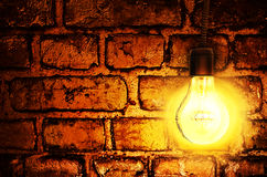 Lamp against the background old brick wall. The bulb burns. Royalty Free Stock Photo