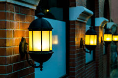 Lamp against a red brick wall at night. Royalty Free Stock Photography