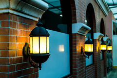 Lamp against a red brick wall at night. Stock Image