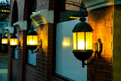 Lamp against a red brick wall at night. Stock Images
