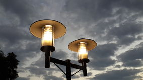 Lamp against the sky. A highly contrasting image of bright yellow lights against a faded grey sky Royalty Free Stock Photography