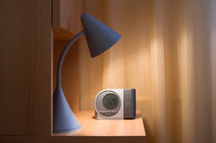 Lamp and alarm clock. Detail of cozy bedroom - reading lamp and alarm clock on bedside table made of wood. Unicolor curtain in the background. Lamp lights and royalty free stock photography