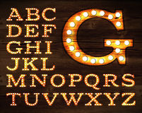 Lamp alphabet old style. Vector of letters in retro style old lamp alphabet for light board on wood background Stock Photography