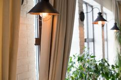 A lamp on the background of a window and a wall with curtains Royalty Free Stock Photos