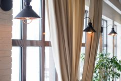 A lamp on the background of a window and a wall with curtains Stock Images