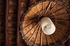 Lamp with bamboo lampshade hanging under the roof stock photos