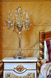 Lamp and bedding in golden decoration. Bedding, furniture and beautiful lamp like candle holder, in comfortable warm color and noble, luxury decorating style Royalty Free Stock Image