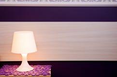 Lamp on bedside table. Closeup of illuminated lamp on bedside table with wooden and purple decorated background Stock Image