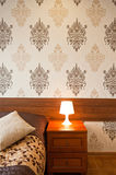 Lamp on bedside table. With patterned wallpaper in background Stock Photo