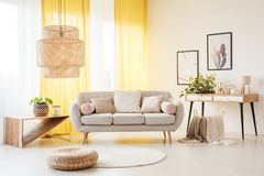 Lamp in bohemian living room. Rattan lamp above pouf and carpet in bohemian living room with settee, plants and yellow curtains stock image