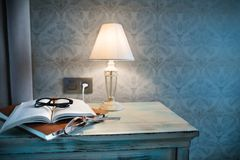 A lamp and a book on a bedside table in a hotel room. A lamp, a book and glasses on a bedside table in a hotel room Royalty Free Stock Images