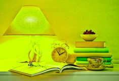 Lamp, books, hours, cup of tea, plate of cherry. Lamp, books, hours, cup of tea, plate of cherry are located on a table Royalty Free Stock Photo