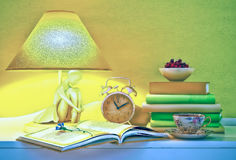 Lamp, books, hours, cup of tea, plate of cherry are located on a table. Evening still life stock images