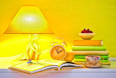Lamp, books, hours, cup of tea, plate of cherry. Royalty Free Stock Photos