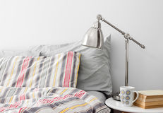 Lamp and books on a side table near bed. With colorful bed linen Stock Photo