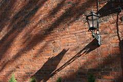Lamp on the brick wall. Fragment of ancient church wall (Old City, Riga, Latvia Royalty Free Stock Photography