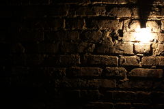 Lamp on the brick wall background. Lamp on a background of a brick wall in a dark room Royalty Free Stock Photos