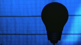 Lamp Bulb with effects of light. Turns on and off with blue background stock video footage