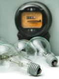 Lamp bulb and electricity supply meter Stock Photos