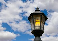 Lamp and Clouds. A street lamp is lit, with a blue and cloudy sky in the background. The lightbulb is energy-efficient fluorescent royalty free stock photo
