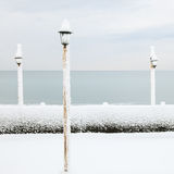 Lamp covered by snow on ocean beach in winter Royalty Free Stock Photos