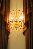 Lamp between curtains. Gold Lamp between luxury curtains stock photo