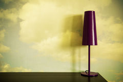 Lamp on desk. Lamp on a desk with clouds on a wall Royalty Free Stock Photo