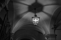 A lamp draws arabesques. Of shadows in the roof of an old building in the evening in a black and white shot Stock Photos