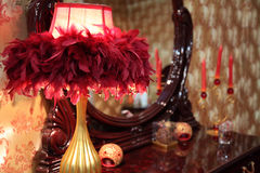 Lamp in feathers on toilet table. Lamp in red feathers on toilet table Stock Image