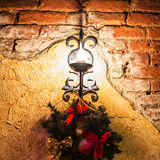 Lamp and fir branch hanging on the wall Royalty Free Stock Photos